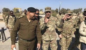 """U.S. Army Lt. Gen. Stephen Townsend talks with an Iraqi officer during a tour north of Baghdad, Iraq, Wednesday, Feb. 8, 2017. Forces fighting the Islamic State group should be able to retake the IS-held cities of Mosul in Iraq and Raqqa in Syria within the next six months, according to the top U.S. commander in Iraq. On a tour north of Baghdad Wednesday, Townsend said """"within the next six months I think we'll see both (the Mosul and Raqqa campaigns) conclude."""" (AP Photo/ Ali Abdul Hassan)"""