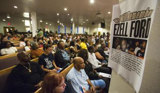 "FILE - In this Aug. 19, 2014, file photo, a poster reads ""We Will Remember Ezell Ford"" at Paradise Baptist Church during a community forum in Los Angeles, to discuss the police shooting of 25-year-old Ezell Ford. The city of Los Angeles will pay $1.5 million to settle a lawsuit brought by the family of  Ford,  who was killed by police during a struggle over an officer's gun. The settlement was approved Wednesday, Feb. 8, 2017, by the Los Angeles City Council after Ezell Ford's family brought a civil rights lawsuit against the city. (AP Photo/Ringo H.W. Chiu, File)"