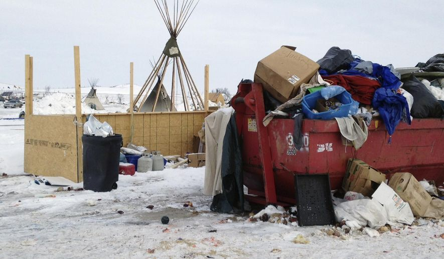 Trash is seen piled in a dumpster at an encampment set up near Cannon Ball, N.D., Wednesday, Feb. 8, 2017, for opponents against the construction of the Dakota Access pipeline. Opponents have called for protests around the world Wednesday, Feb. 8, 2017, as the Army prepared to green-light the final stage of the $3.8 billion project's construction. The Army said Tuesday, Feb. 7, that it will allow the four-state pipeline to cross under a Missouri River reservoir in North Dakota, the last big chunk of construction. (AP Photo/James MacPherson)