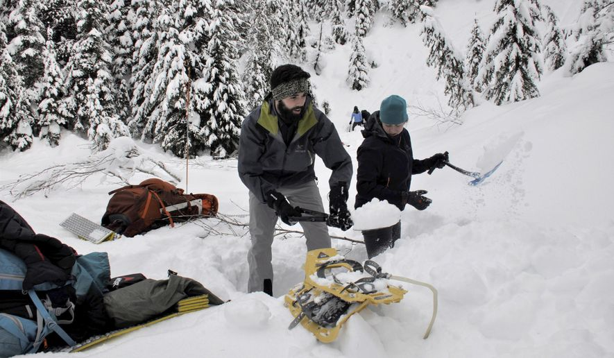 Seth Flanders and Leslie Hvozda begin digging a snow cave near Lookout Pass Idaho, Saturday, Jan. 28, 2017, during an overnight snowshoeing trek with the Spokane Mountaineers. (Rich Landers/The Spokesman-Review via AP)