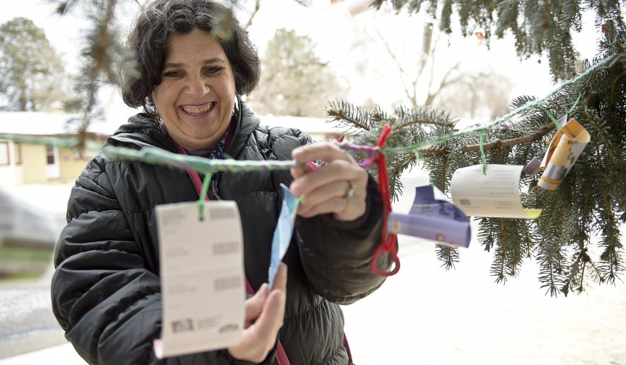 Amy Heneghan hangs a message on the Positivi-Tree in Loomiller Park on Feb. 2, 2017 in Longmont, Colo. Heneghan has been the keeper of the 30-foot blue spruce in the northeast corner of the park, where she and others have been hanging positive messages written on paint samples in all colors from the tree's lower branches.   (Lewis Geyer/The Daily Times Call via AP)