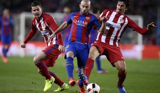 Barcelona's Javier Mascherano, center, fights for the ball with Atletico's Lucas Hernandez and Stefan Savic, right, during the the Copa del Rey semifinal second leg soccer match between FC Barcelona and Atletico Madrid at the Camp Nou stadium in Barcelona, Spain, Tuesday Feb. 7, 2017. (AP Photo/Manu Fernandez)