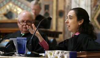 FILE - In this Sept. 18, 2014, file photo, Circuit Judge Michelle T. Friedland, right, gestures while questioning Barry Bonds' attorney, Dennis Riordan, before an 11-judge panel of the 9th U.S. Circuit Court of Appeals in San Francisco. Friedland is one of three judges on the San Francisco-based 9th Circuit Court of Appeals deciding whether to reinstate President Donald Trump's travel ban. (AP Photo/Eric Risberg, Pool, file)