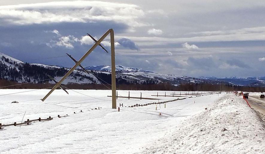 Downed power lines and polls are shown along the Moose-Wilson Road near Teton Village, Wyo. Wednesday, Feb.8, 2017, after an overnight storm blew through the area. Wind gusts of up to 90 mph were reported in west-central Wyoming Tuesday night, but a Lower Valley Energy source said it's not clear if it was straight winds, microbursts or something else that bent some of the steel poles over like they were made of balsa wood. (Brian Tanabe/Lower Valley Energy via AP)