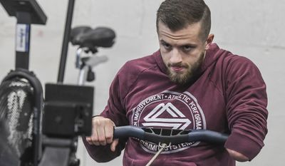 In this Jan. 20,  2017 file photo, CrossFit coach Casey Acree who was born without part of his left arm, works out at Kirby Medical Center in Monticello, Ill.  (Clay Jackson/Herald & Review via AP) **FILE**