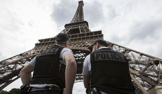 French riot police officers patrol under the Eiffel Tower, near the entrance of the soccer fan zone, prior to the Euro 2016 Group A soccer match between France and Romania, in Paris, June 10, 2016. (Associated Press) ** FILE **