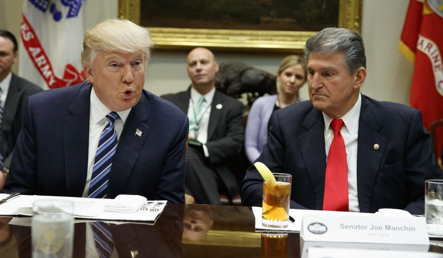 In this file photo, Sen. Joe Manchin, D-W.Va., listens at right as President Donald Trump speaks during a meeting with Senators on his Supreme Court Justice nominee Neil Gorsuch, Thursday, Feb. 9, 2017, in the Roosevelt Room of the White House in Washington. (AP Photo/Evan Vucci) **FILE**