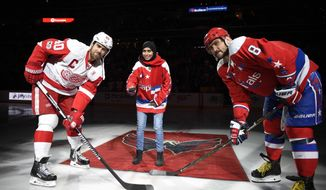 Fatima Al Ali, of the United Arab Emirates, center, takes part in a ceremonial puck drop before an NHL hockey game with Washington Capitals left wing Alex Ovechkin (8), of Russia, and Detroit Red Wings left wing Henrik Zetterberg (40), of Sweden, Thursday, Feb. 9, 2017, in Washington. (AP Photo/Nick Wass)