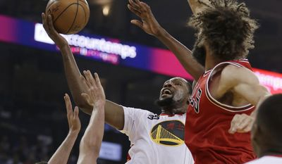 Golden State Warriors forward Kevin Durant, center, shoots between Chicago Bulls' Paul Zipser, left, and Robin Lopez during the first half of an NBA basketball game Wednesday, Feb. 8, 2017, in Oakland, Calif. (AP Photo/Ben Margot)