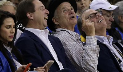 Actor Bill Murray, center, gestures beside Golden State Warriors co-owner Joe Lacob, left, during the first half of the Warriors' NBA basketball game against the Chicago Bulls on Wednesday, Feb. 8, 2017, in Oakland, Calif. (AP Photo/Ben Margot)