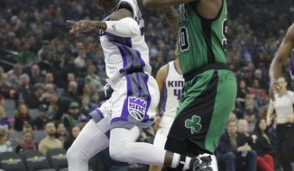 Sacramento Kings guard Darren Collison, left, hits the ball out of the hands of Boston Celtics forward Amir Johnson during the first quarter of an NBA basketball game, Wednesday, Feb. 8, 2017, in Sacramento, Calif. (AP Photo/Rich Pedroncelli)