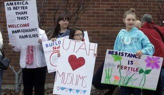 People hold their signs as they gather outside the Brighton High School before U.S. Rep. Jason Chaffetz town hall meeting Thursday, Feb. 9, 2017, in Cottonwood Heights, Utah. His visit came as the congressman spends time in his home state, visiting with Muslim leaders and holding a town hall Thursday night in which he's expected to be greeted by a small band of protesters and face some sharp questions from constituents who are frustrated about his refusal to investigate President Donald Trump's ties to Russia. (AP Photo/Rick Bowmer)