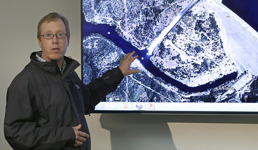 Eric See, of the California Department of Water Resources, gestures to an aerial photo of the Oroville Dam spillway during a news conference, Thursday, Feb. 9, 2017, in Oroville, Calif. Earlier this week, chunks of concrete went flying off the spillway, creating a 200-foot-long, 30-foot deep hole. (AP Photo/Rich Pedroncelli)