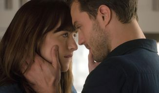 "This image released by Universal Pictures shows Dakota Johnson as Anastasia Steele, left, and Jamie Dornan as Christian Grey in ""Fifty Shades Darker."" (Doane Gregory/Universal Pictures via AP)"