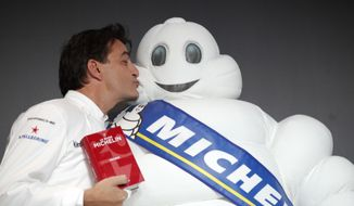 French chef Yannick Alleno who runs Le 1947 restaurant in Courchevel, gives a kiss to the Michelin Mascot known as Bibendum after being awarded three stars from the Michelin guide, Thursday, Feb.9, 2017 in Paris. One restaurant was newly awarded with the prestigious 3 stars this year. (AP Photo/Christophe Ena)