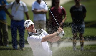 Marc Warren of Scotland follows his shot on the third hole during the first day of Maybank Championship golf tournament in Kuala Lumpur, Malaysia on Thursday, Feb. 9, 2017. (AP Photo/Vincent Thian)