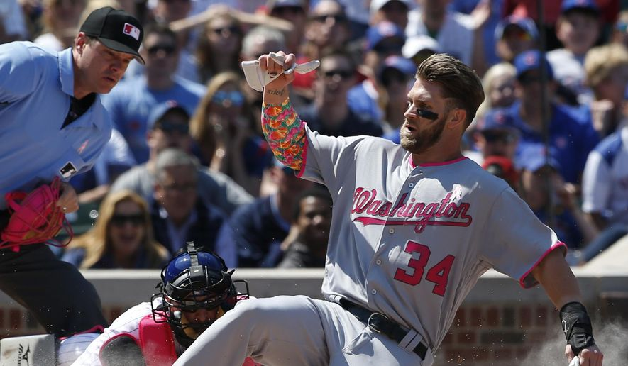 FILE - In this May 8, 2016, file photo, Washington Nationals' Bryce Harper scores on a double by Ryan Zimmerman as Chicago Cubs catcher Tim Federowicz applies a late tag during the third inning of a baseball game in Chicago. Instead of revamping their roster after yet another early playoff exit, the Washington Nationals head to spring training next week counting on a bounce-back year from Bryce Harper and a full season from Stephen Strasburg. (AP Photo/Nam Y. Huh, File)