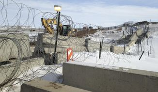 Razor wire and concrete barriers protect access to the Dakota Access pipeline drilling site Thursday, Feb. 9, 2017 near Cannon Ball, North Dakota. The developer says construction of the Dakota Access pipeline under a North Dakota reservoir has begun and that the full pipeline should be operational within three months. One of two tribes who say the pipeline threatens their water supply on Thursday filed a legal challenge asking a court to block construction while an earlier lawsuit against the pipeline proceeds. (AP Photo/James MacPherson)