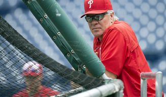 FILE- In this July 4, 2016, file photo, Philadelphia Phillies manager Pete Mackanin watches from behind the batting cage before a baseball game against the Atlanta Braves in Philadelphia. After improving from 63 wins in 2015 to 71 in 2016, manager Pete Mackanin wants his players to aim for 81 this season. (AP Photo/Chris Szagola, File)