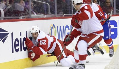 Detroit Red Wings defenseman Jonathan Ericsson (52), of Sweden, slams into the boards during the first period of an NHL hockey game against the Washington Capitals, Thursday, Feb. 9, 2017, in Washington. Washington Capitals center Nicklas Backstrom (19), of Sweden, was called for boarding on the play. (AP Photo/Nick Wass)