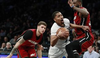 Brooklyn Nets guard Spencer Dinwiddie, center, collides with Miami Heat forward Willie Reed, right, as guard Tyler Johnson watches during the second half of an NBA basketball game, Friday, Feb. 10, 2017, in New York. The Heat won 108-99. (AP Photo/Julio Cortez)