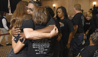 Rochelle Hamm, second from left, the wife of El Faro crew member Frank Hamm, is embraced by the family members of other El Faro crew members after they posed with photographs of their loved ones during a break in a U.S. Coast Guard investigative hearing, Friday, Feb. 10, 2017 in Jacksonville, Fla. The 790-foot freighter heading from Jacksonville, Fla., to San Juan, Puerto Rico sailed into the eye of Hurricane Joaquin near the Bahamas on Oct. 1, 2015 and sank, killing all 33 crew members. (Bob Self/The Florida Times-Union via AP)