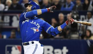 FILE - In this Oct. 4, 2016, file photo, Toronto Blue Jays' Jose Bautista hits a solo home run against the Baltimore Orioles during the second inning of an American League wild-card baseball game in Toronto. Bautista, languished on the market for months before signing a one-year, $18.5 million deal to return to the Blue Jays. His deal includes a mutual option for 2018, and vesting options for 2019.  (Nathan Denette/The Canadian Press via AP, File)