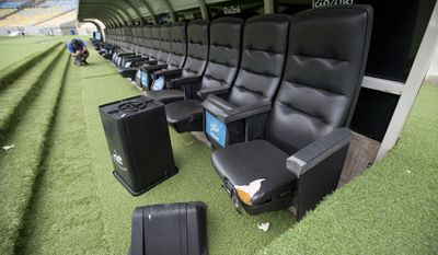 "In this Feb. 2, 2017 photo, a trash can lays by ripped seats at one of the dugouts in Maracana stadium in Rio de Janeiro, Brazil. ""The Maracana is the biggest symbol of the way the games were managed,"" said Mauricio Santoro, a political scientist at Rio de Janeiro State University. ""The vast majority of people in Rio will never go the golf course, or the Olympic venues. But the Maracana is different. It's the jewel of the crown."" (AP Photo/Silvia Izquierdo)"