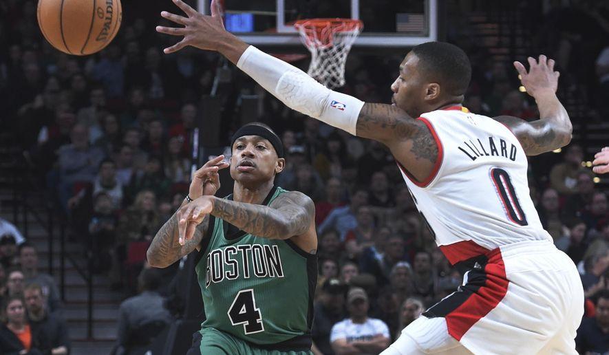 Boston Celtics guard Isaiah Thomas passes the ball past Portland Trail Blazers guard Damian Lillard during the first half of an NBA basketball game in Portland, Ore., Thursday, Feb. 9, 2017. (AP Photo/Steve Dykes)