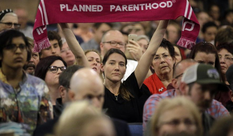 A person supporting Planned Parenthood looks on during Rep. Jason Chaffetz's town hall meeting at Brighton High School, Thursday, Feb. 9, 2017, in Cottonwood Heights, Utah. Hundreds of people lined up early for a town hall with Chaffetz on Thursday evening, many holding signs criticizing the congressman's push to repeal the newly-named Bears Ears National Monument in southern Utah. (AP Photo/Rick Bowmer)