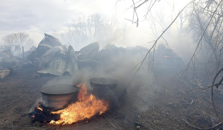 Tractor tires burn near the remains of one of three barns destroyed by a fire at Frog Belly Farm, 5255 W. Rogers Rd., west of Longmont, Colo., Friday, Feb. 10, 2017. (Lewis Geyer/The Daily Times Call via AP)