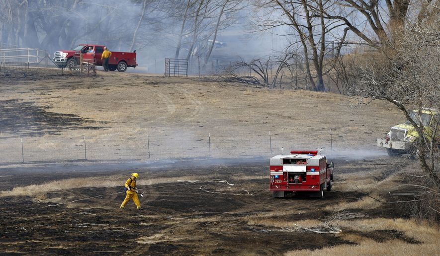 Firefighters mop up after a fire west of Longmont, Colo., Friday, Feb. 10, 2017. About 300 homes were evacuated because of two fires being pushed by gusty winds in Boulder County. One burned in a relatively flat, open area near some farms and clusters of homes west of Longmont on Friday. The other was burning in the foothills west of Boulder. (AP Photo/Brennan Linsley)