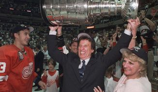 CORRECTS RED WINGS PLAYER TO VYACHESLAV KOZLOV, INSTEAD OF IGOR LARIONOV - FILE - In this June 17. 1998, file photo, Detroit Red Wings owner Mike Ilitch, center, hoists the Stanley Cup in Washington after the Red Wings won their second consecutive NHL championship. Vyacheslav Kozlov is at left. Ilitch, founder of the Little Caesars Pizza empire and owner of the Red Wings and the Detroit Tigers, has died. He was 87. Ilitch, who was praised for keeping his professional hockey and baseball teams in Detroit as other urban sports franchises relocated to new suburban stadiums, died Friday, Feb. 10, 2017, at a hospital in Detroit, according to family spokesman Doug Kuiper. (Julian H. Gonzalez/Detroit Free Press via AP)