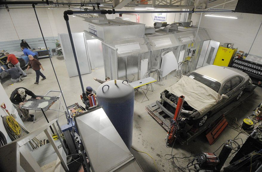 In this Feb. 1, 2017 photo, Students work inside the Erie Institute of Technology auto body technician lab in Erie, Pa. The institute calls the building an auto body technician lab, but it looks, sounds, smells and feels more like a garage. The school sees this building, outfitted with a lift, paint booth and frame-straightening machine, as a place where students can take the first steps toward a new career. (Greg Wohlford/Erie Times-News via AP)