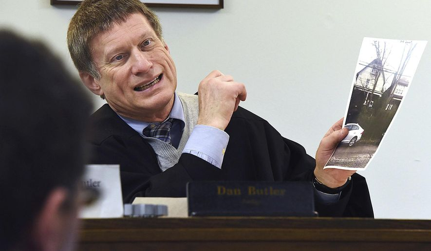 ADVANCE FOR RELEASE SATURDAY, FEB. 11, 2017, AT 3:01 A.M. EST. AND THEREAFTER - In this Jan. 23, 2017 photo, District Justice Dan Butler, in the Squirrel Hill neighborhood of Pittsburgh courtroom, holds up a photo and talks about violations in the front yard during hearings on Housing Code. Ask any district judge to describe his weirdest case to date and he'll stare at the air awhile, considering the treasures to choose from. (Darrell Sapp/Pittsburgh Post-Gazette via AP)