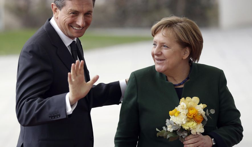 German Chancellor Angela Merkel, right, welcomes the President of Slovenia, Borut Pahor, left, for a meeting at the chancellery in Berlin, Germany, Wednesday, Feb. 8, 2017. (AP Photo/Michael Sohn)