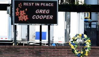 FILE - In this April 12, 2016, file photo, a wreath and a sign show the mourning of the loss  Greg Cooper,  a worker at the Goodyear plant in Danville, Va. Goodyear will pay $1.75 million to settle workplace health and safety violations found in inspections following four deaths at its Danville tire plant. The Virginia Department of Labor and Industry announced the penalties Friday, Feb. 10, 2017. (Matt Bell/Register & Bee via AP)/