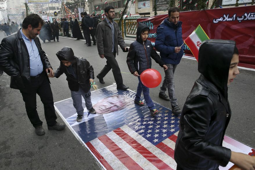 Iranians march on a portrait of U.S. President Donald Trump and the picture of U.S. flag in an annual rally commemorating the anniversary of the 1979 Islamic revolution, which toppled the late pro-U.S. Shah, Mohammad Reza Pahlavi, in Tehran, Iran, Friday, Feb. 10, 2017. (AP Photo/Vahid Salemi)