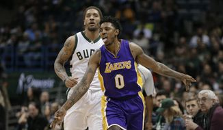 Los Angeles Lakers' Nick Young (0) reacts after his 3-point basket in front of Milwaukee Bucks' Michael Beasley during the second half of an NBA basketball game Friday, Feb. 10, 2017, in Milwaukee. (AP Photo/Jeffrey Phelps)