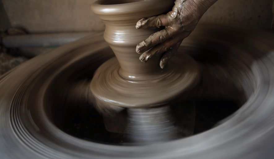 In this Wednesday, Jan. 25, 2017 photo, a Nepalese Prajapati potter moulds a clay pot in a potters wheel in the ancient Nepali town of Thimi. For generations, the residents of Thimi supplied the rest of the Himalayan country everything from tiny clay lamps used in temples to massive grain storage jars. As more young people leave town for better paying jobs in other parts of Nepal or abroad, fewer families have to eke out an income from the relatively low-returns business of clay pottery. Of the nearly 2,000 Prajapati families in town, less than 300 families now depend on clay pottery for a living. (AP Photo/Niranjan Shrestha)