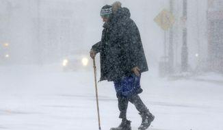Todd Fike, crosses the street during a snowstorm, Thursday, Feb. 9, 2017, in Framingham, Mass. (AP Photo/Steven Senne)