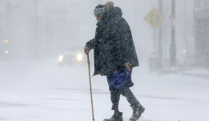 Todd Fike, crosses the street during a snowstorm, Thursday, Feb. 9, 2017, in Framingham, Mass. (AP Photo/Steven Senne)