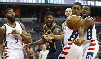 Washington Wizards guard Bradley Beal (3), with teammates Markieff Morris (5), Marcin Gortat, of Poland, back center, and John Wall, right, nearby, eyes the the ball for a rebound while Indiana Pacers forward Paul George (13) watches during the first half of an NBA basketball game in Washington, Friday, Feb. 10, 2017. (AP Photo/Manuel Balce Ceneta)