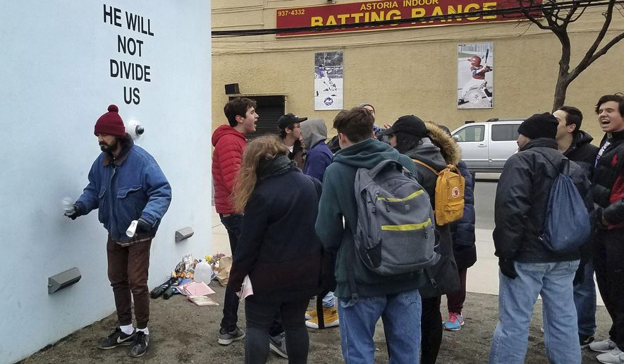 """FILE- In this undated photo, actor Shia LeBeouf, left, stands in front of a live-steam camera with the words """"HE WILL NOT DIVIDE US"""" posted on a wall outside of the the Museum of the Moving Image as members of the public join LeBeouf in chanting the words """"He will Not Divide Us"""" in the Queens borough of New York. The Museum of the Moving Image closed the performance on Friday, Feb. 10, 2017, citing """"serious public safety hazards."""" (AP Photo/Deepti Hajela, File)"""