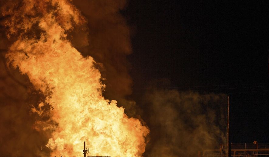Vehicles and a power pole smoke next to a fire at the Phillips 66 pipeline in Paradis, La. Thursday, Feb. 9, 2017. Authorities don't yet know what caused the fire on the pipeline in Paradis, but several workers was cleaning it at the time, St. Charles Parish Sheriff Greg Champagne said at a news conference. (Matthew Hinton/The Advocate via AP)