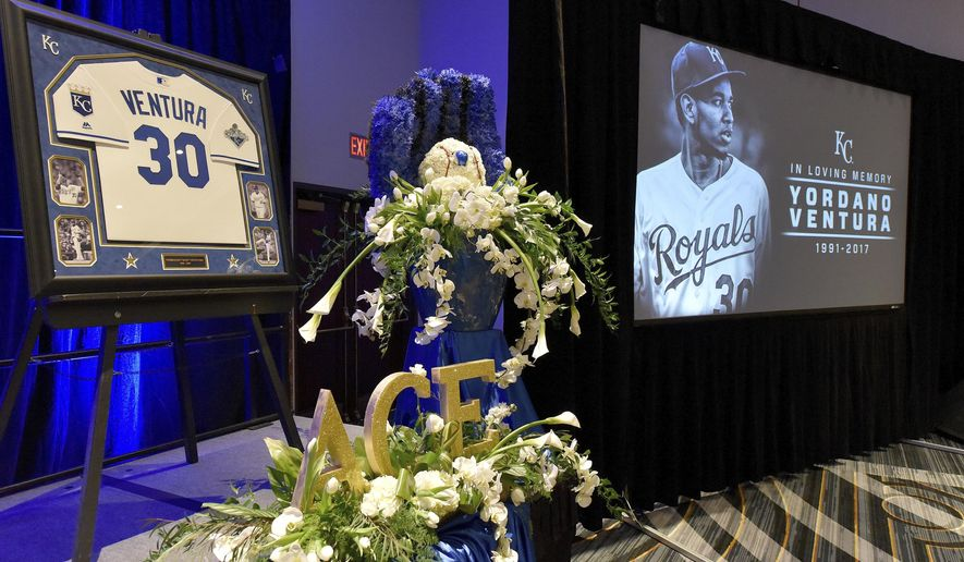 FILE - In this Jan. 27, 2017, file photo, flowers, images and a jersey are among the items at the front of the room where Kansas City Royals' Yordano Ventura was remembered by members and employees of the baseball team in Kansas City, Mo. The Royals are reporting to spring training in Arizona with expectations of competing for another AL Central title after missing the postseason a year ago. But the task became even more challenging after the death of young flamethrower Yordano Ventura, who was killed in a car crash in the Dominican Republic. (John Sleezer/The Kansas City Star via AP, File)