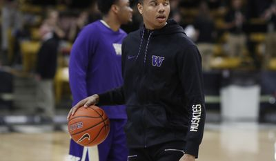 Washington guard Markelle Fultz dribbles a ball as his teammates warm up for an NCAA college basketball game against Colorado on Thursday, Feb. 9, 2017, in Boulder, Colo. Fultz, projected as a top pick in this year's NBA draft, is sitting out the game because of a sore knee. (AP Photo/David Zalubowski)