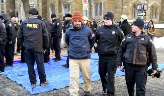 John Lugo, center, of Unidad Latina en Accion of New Haven, is arrested during a demonstration after some protesters blocked the intersection of Elm and College Streets in New Haven, Conn., Friday, Feb. 10, 2017, and refused to move. The protesters are in favor of changing the name of Yale University's Calhoun College. The peaceful arrests were pre-planned and coordinated between the demonstrators and New Haven Police. (Peter Hvizdak/New Haven Register via AP)