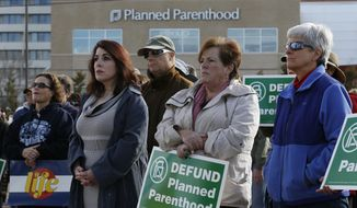 Participants in an anti-abortion rally hold signs and listen to a speaker in front of Planned Parenthood of the Rocky Mountains, in Denver, Saturday, Feb. 11, 2017.  Rallies aimed at urging Congress and President Donald Trump to end federal funding for Planned Parenthood are scheduled across the country.  (AP Photo/Brennan Linsley)