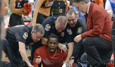 A fan is tackled by arena security and Louisville police after running onto the court during a timeout at the Miami against Louisville NCAA college basketball game, Saturday, Feb. 11, 2017, in Louisville, Ky. (AP Photo/Timothy D. Easley)